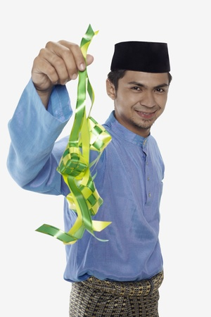 three people only: Man in traditional clothing holding ketupat Stock Photo