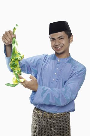 Man in traditional clothing holding ketupat Standard-Bild