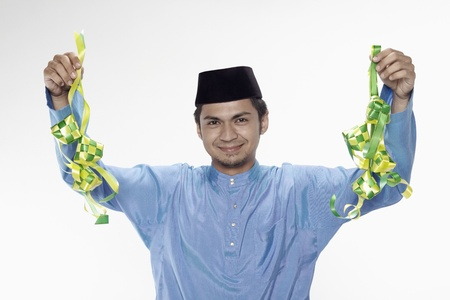 culture decoration celebration: Man in traditional clothing holding ketupat Stock Photo