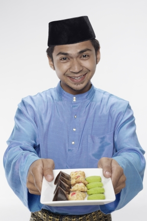 malay food: Man in traditional clothing holding a plate of cookies
