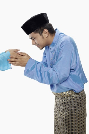 Man in traditional clothing greeting another person