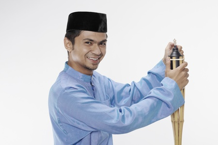 Man in traditional clothing lighting up oil lamp photo