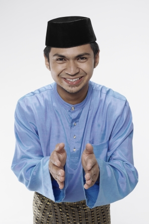 Man in traditional clothing showing greeting gesture photo