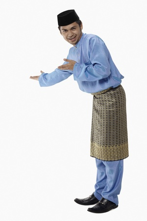 Man in traditional clothing showing greeting gesture