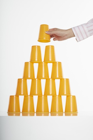 Hand placing disposable cup on top of stack Stock Photo - 19285018