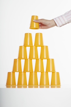 out of control: Hand placing disposable cup on top of stack