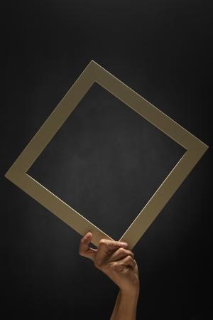 efectos especiales: La mano del hombre la celebración de un marco en blanco Foto de archivo
