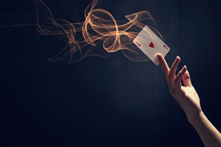 Human hand holding up an ace of hearts