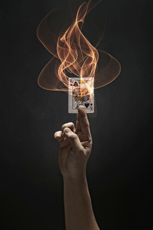 burning man: Human hand holding a King of Spades card