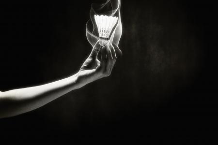 Human hand holding up a shuttlecock