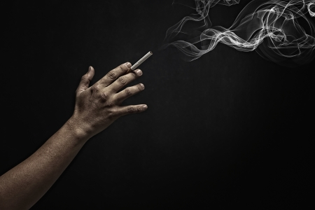 side effect: Human hand holding a burning cigarette