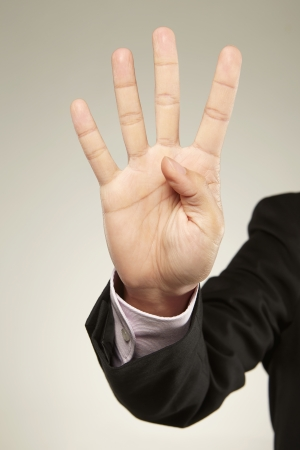 Person holding up four fingers photo