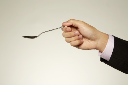 Human hand holding a silver spoon Stock Photo