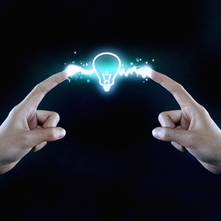 side effect: Illuminated light bulb in the middle of two fingers Stock Photo