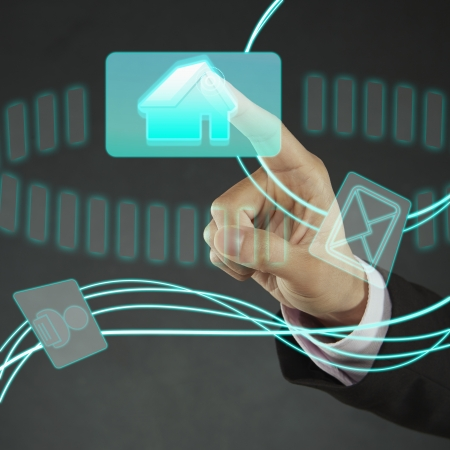 ownership and control: Index finger pointing at a Home icon Stock Photo