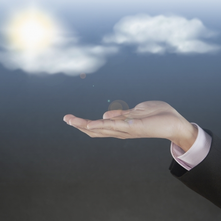 Sun and clouds floating above human hand photo