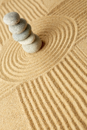 Pebble Beach: Stack of pebbles on the wave pattern in the sand Stock Photo