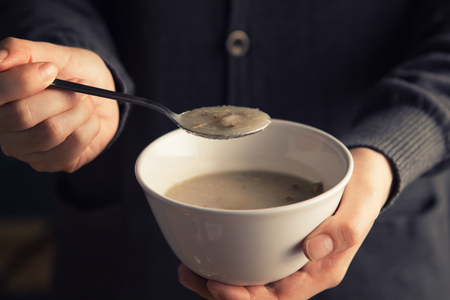 Person scooping mushroom soup Stock Photo