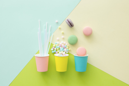 Sweet indulgence and cups concept on pastel background