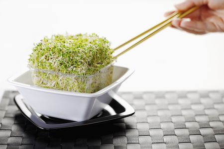 Human hand using chopsticks to eat bean sprouts salad Stock Photo - 6513499