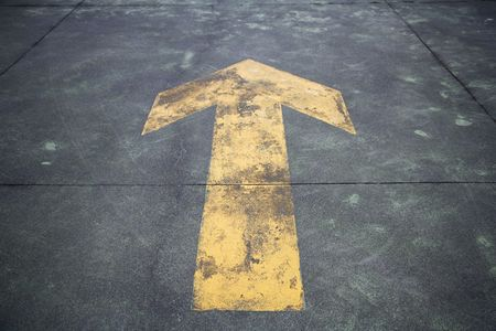 Directional arrow painted on the street, close-up photo