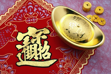 Gold ingot on decoration paper with gold coins photo