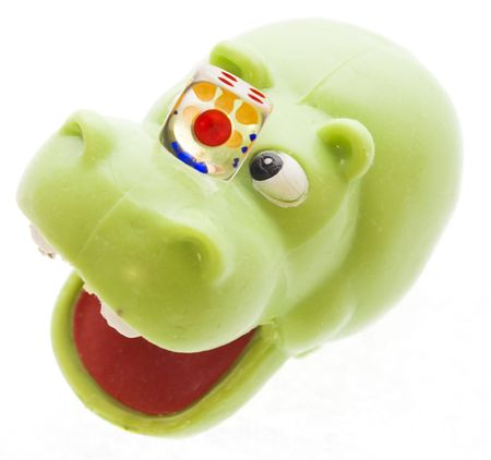The toy hippopotamus holds dice on a nose Stock Photo - 2683373