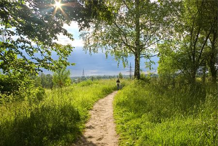 The ray of light makes the way through foliage of a tree. A footpath in a grass. On a footpath in the distance there are two children. On horizon dark clouds and transmission lines. photo