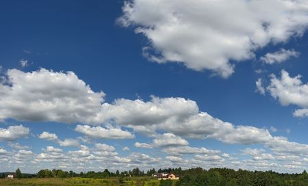 horizont: High clouds on high sky. Small houses near horizont. Stock Photo