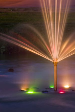 The fountain in park is shined by multi colored lanterns. Long shutter