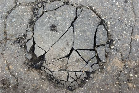 Very old asphalt - set of the cracks, damaged by weather. Small stones are visible.