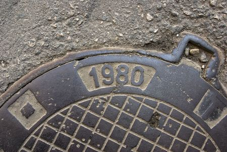 nine years old: Metal manhole. On a hatch cover it is printed creation date. Outdoor.