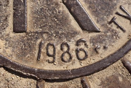 Metal manhole. On a hatch cover it is printed creation date. Outdoor.