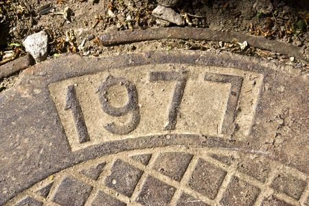 nine years old: Metal  manhole. On a hatch cover it is printed creation date. Outdoor. Stock Photo