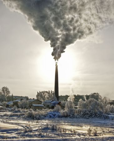 chimneys: Smoke of thermal station. Frosty (cold) day. It is photographed against the sun. It is processed in graphic programs. Stock Photo