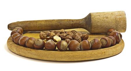 bonkers: large dark hazelnuts. On a wooden cutting board.