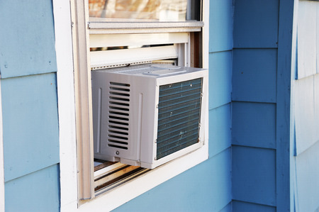 old air conditioner installed on house window Stok Fotoğraf