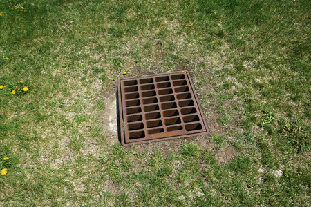 grate: sewer grate on the lawn for heavy rain