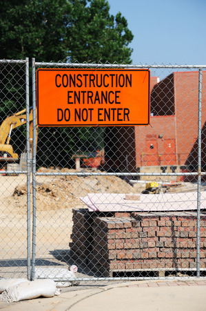 construction material: Construction site with construction material, iron fence and warning message board