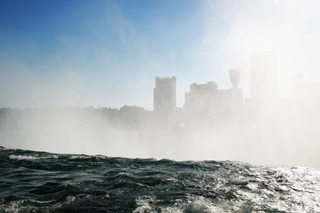 niagara falls city: mist from Niagara Falls in the sky before city skyline Stock Photo