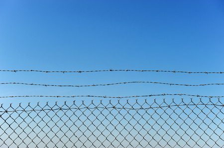 chainlink fence: chainlink fence against blue sky
