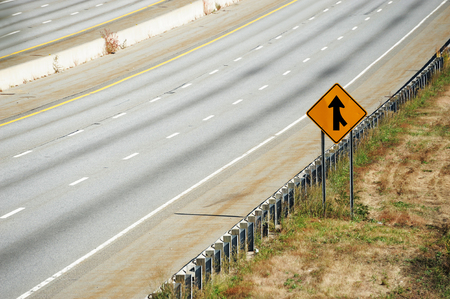 merge: merge sign by the side of multi-lane highway Stock Photo