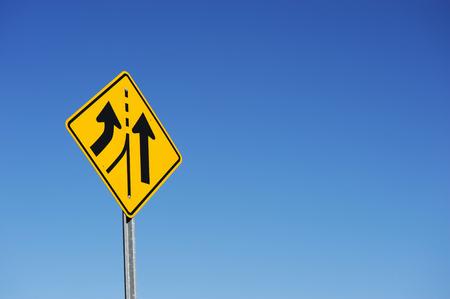Verkehrszeichen gegen den blauen Himmel im Hintergrund verschmelzen