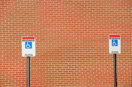 brick sign: handicap sign in parking area against brick wall Stock Photo
