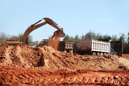 dumper truck: excavator, loading dumper truck with dirt in construction site