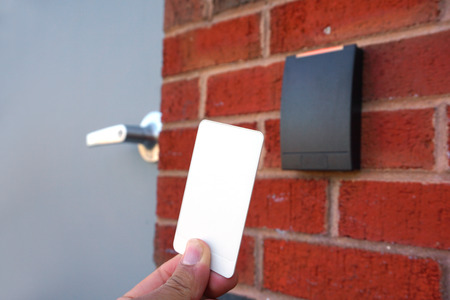 using white entrance card at door entrance card reader