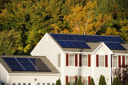 Zonnepaneel geïnstalleerd op het huis dak met herfst bomen Stockfoto