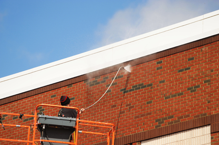 outdoor worker cleaning the exterior wall of building through pressure water Stock Photo