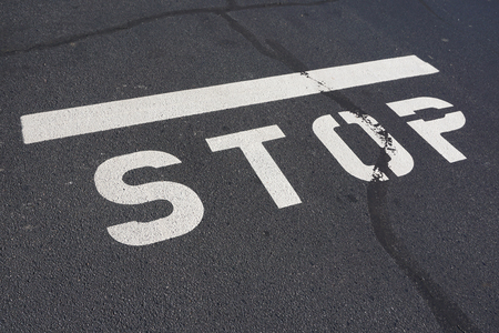 road surface: stop text sign painted on the asphalt road surface