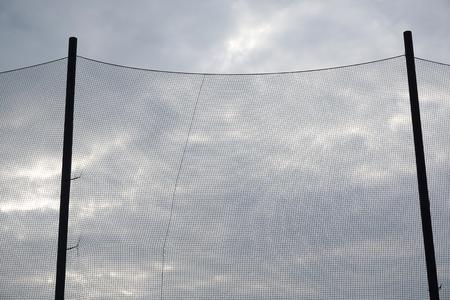 ballpark: backstop net and stadium lights at baseball or softball playing field